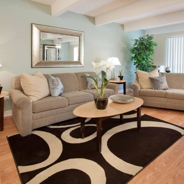 Mosaic Apartments - Living Room with Two Couches and Three Tables.