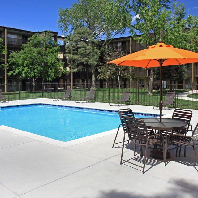 Mosaic Apartments - Outdoor table with Pool in view.