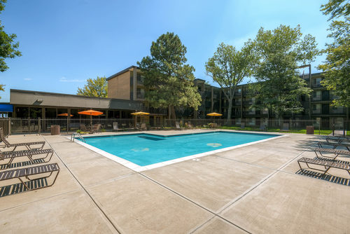 Mosaic Apartments - Pool with Chairs and Apartments in view.